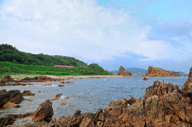 写真: 行合崎の岩場を行く五能線ローカル列車