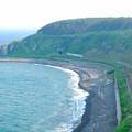 写真: 夏の朝の海岸を行く