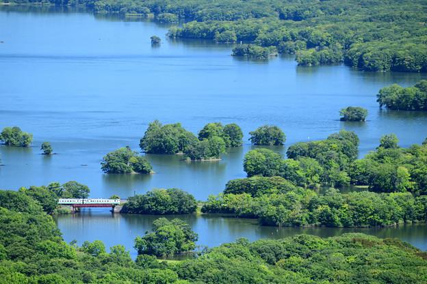 青い空を湖面に映して一筋の線路を行くローカル列車