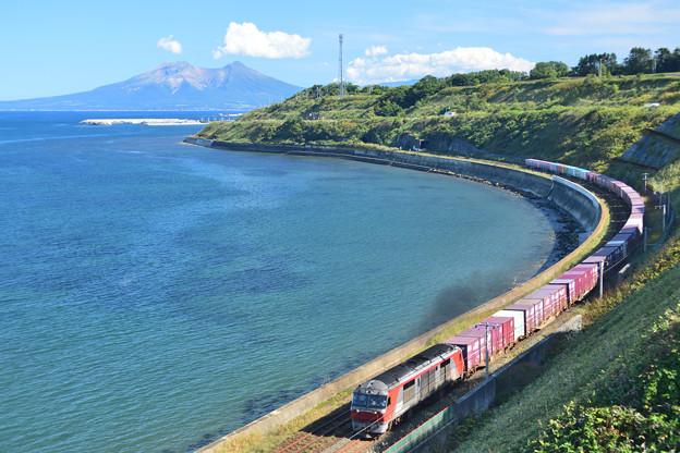 駒ヶ岳をバックに噴火湾を行く貨物列車