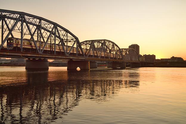 日没の荒川橋梁を渡る京成電車