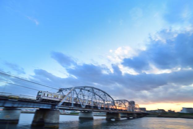 夕暮れの鉄橋を渡る電車