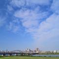 空を埋める雲と荒川橋梁を渡る京成電車