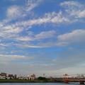 踊るような雲が広がる鉄橋と電車