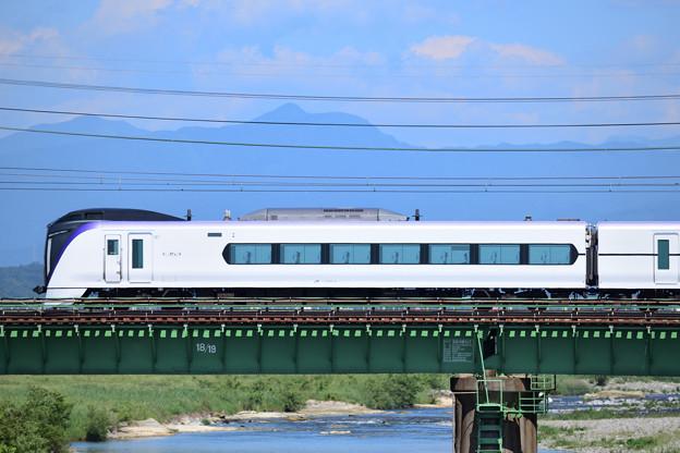 奥多摩の山々を背景に多摩川橋梁を渡るE351系特急電車
