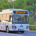 """写真: """"間接的""""に西陽を映し出しながら走るバス"""