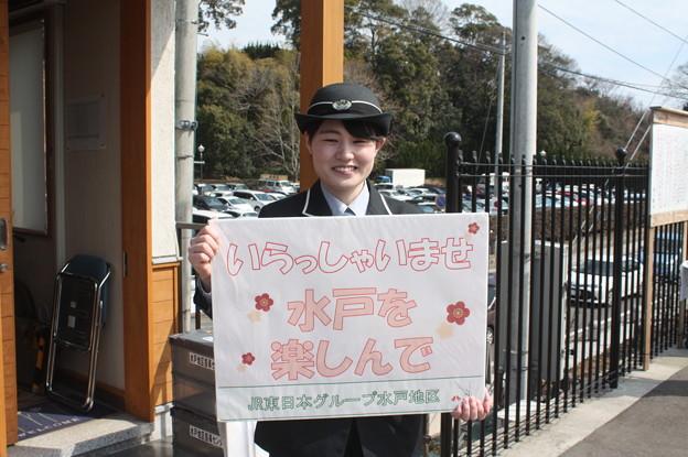 偕楽園駅で梅まつりのボードを持つ女性駅員