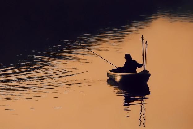 写真: 湖上の釣り人