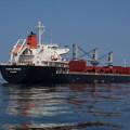 錨地でハッチカバーを操作中のバラ積み貨物船
