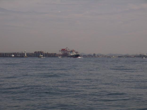 汽笛を鳴らしながら釣船群の中を出港する貨物船