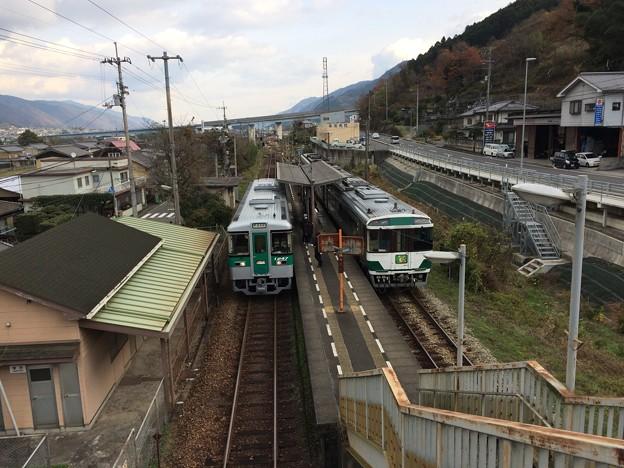 佃駅に停車中の普通列車と特急列車