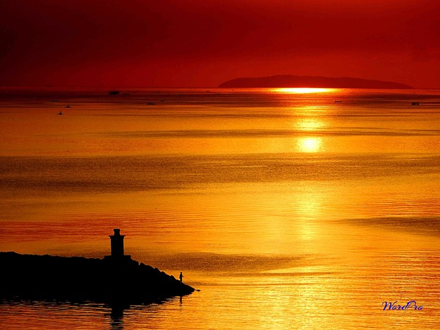 コレヒドール島と夕陽の釣り人