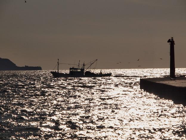 夕暮れの海原の漁船