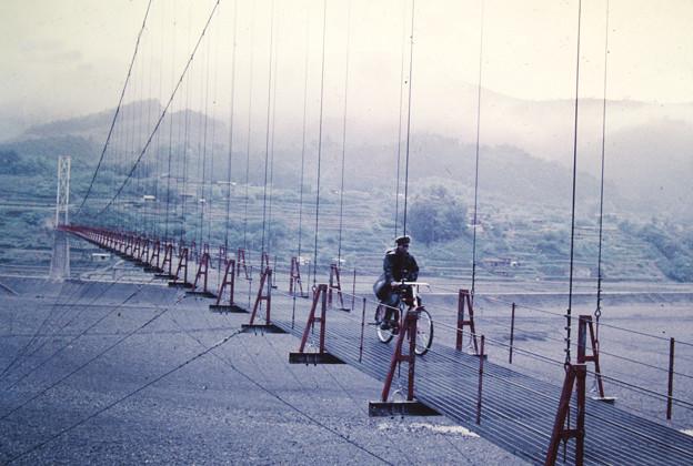 自転車で吊り橋を渡る郵便屋さん