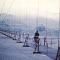 Photos: 自転車で吊り橋を渡る郵便屋さん