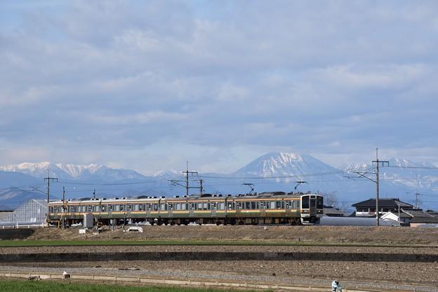 雪の男体山と両毛線211系