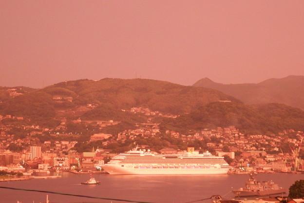 写真: 赤い空とコスタ・セレーナと護衛艦