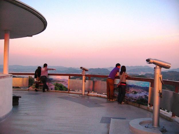写真: 千光寺公園の展望台から瀬戸の夕景を楽しむ若いカップル達