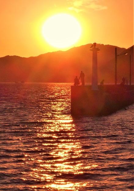 夕暮れの荒海と釣り人たち