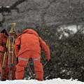 写真: 吹雪の中の測量作業
