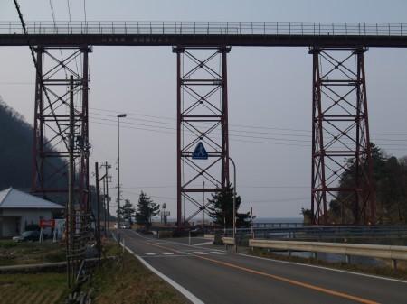 橋の下には道路が交差しており、車が米粒のように見える