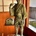 写真: 天秤棒を担いだ近江商人の像