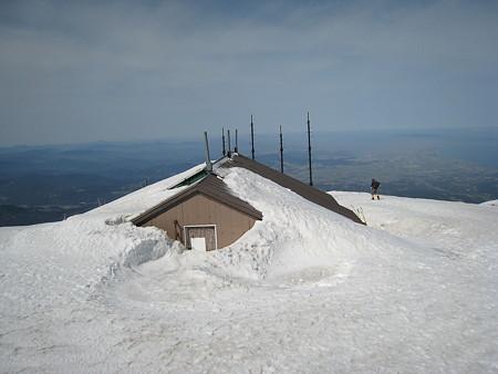 雪に埋まる山頂避難小屋