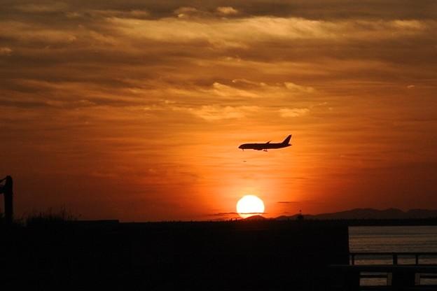 慶良間の島影に沈む夕陽と旅客機